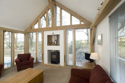 Glazed green oak gable with contemporary stove in Tin House in Dartmoor National Park by Roderick James Architects