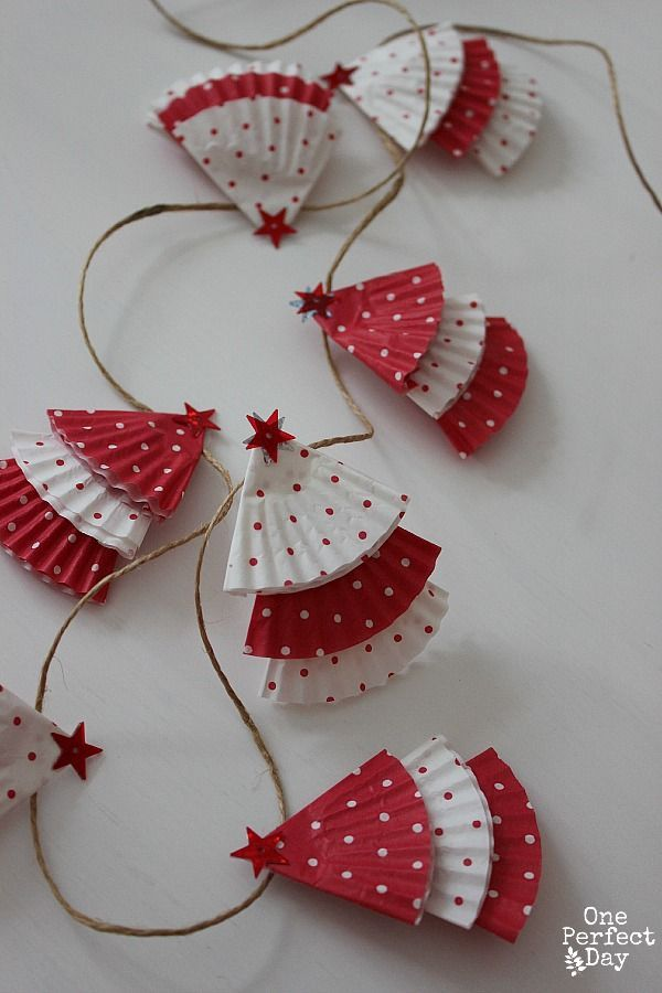 Cupcake liner Christmas garland (or ornaments), even kids can make. = Made Dec. 2015 w/ Rachel & Elizabeth. Turned out darling! We used star shaped brads at the top (because the store was out of star sequence) and we like them better. They add some dimension to the trees. It really doesn't take very many liners, so now I have TONS left over...