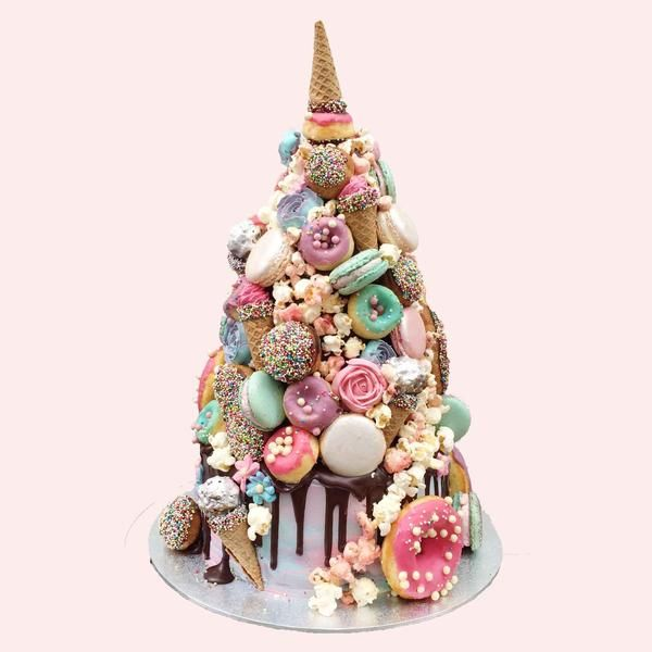 """Croquembouche unicorn cake -- """"It looked more magical as we kept building it up with sprinkle glazed profiteroles and eclairs, colourful macarons, pretty pastel baked doughnuts, piped buttercream flowers, chocolate pearls, Ferrero rocher cones, """"soft serve"""" buttercream cones and candied popcorn. And WOW. Just look at it!"""""""
