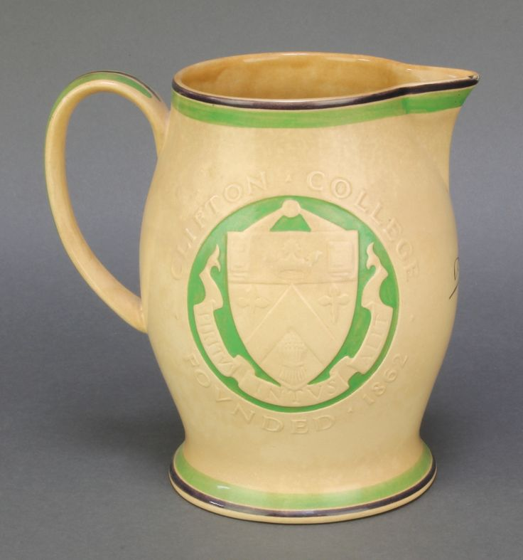 """Lot 46, Ashtead Pottery, a tan glazed pottery jug to commemorate Clifton College founded 1862, a first edition strictly limited to  300 jugs being no. 44,  bearing the signatures of DP Percival and the artist Allan G Wyon 7 1/2"""", est £50-80"""