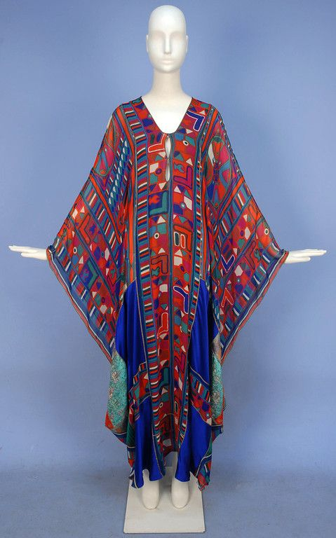 """THEA PORTER COUTURE SILK CHIFFON PATCHWORK ABAYA, c. 1970. Vibrant stylized tribal print caftan having slashed neckline, metallic piping and side tassels, lower front pieced in cobalt satin and various Indian metallic brocades, """"Thea Porter"""" incorporated in chiffon print."""