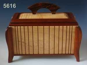 This burial urn is shaped as a more traditional rectangular box with lid and angled legs