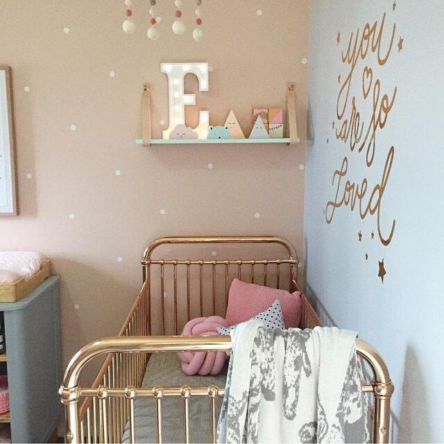 Small white vinyl polka dot wall stickers on a brown wall in a children's nursery. The vinyl dots are evenly spaced to create a uniform dot wallpaper replacement.