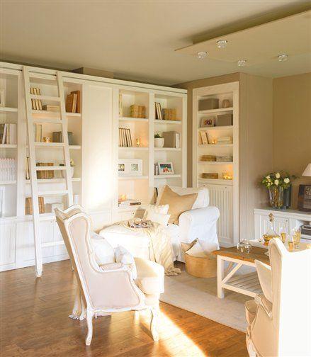 Salón con butacas claras y librería blanca