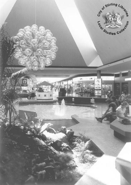 Interior of Karrinyup Shopping Centre when there was still a pool in the central area, 1970s [photograph].
