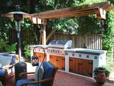 A wooden pergola shades this Southwestern-style outdoor kitchen. Complete with a grill, Old World-inspired wood cabinets and ample counter space, it's just steps away from a brick patio with comfy seating.