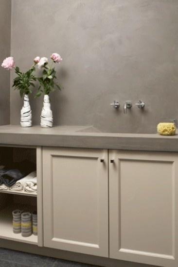Badkamer met betonlook wanden en unieke wastafel. Door betonlookdesign
