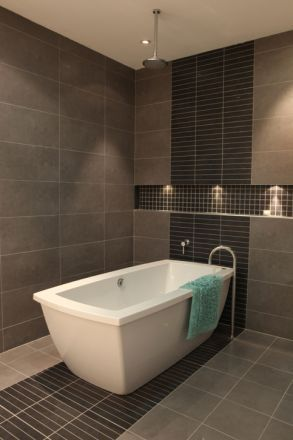 Rain shower over a deep, freestanding bath. Gorgeous integrated floor to ceiling tiling.