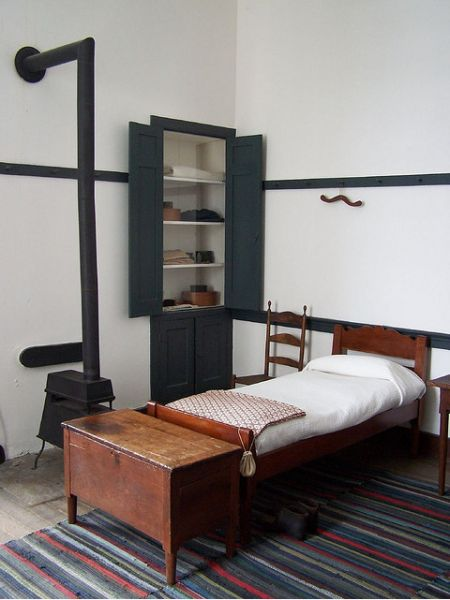 Wonderful Composition. Shaker style bed. Wood burning stove built in cabinet. White walls and wood floor
