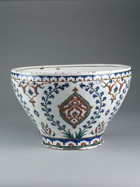 Bowl Place of origin: Iznik, Turkey (made) Turkey (probably) Date: ca. 1575-1600 Bowl of fritware, painted in red, blue and green on a white ground with a repeating design of pointed medallions filled in with arabesques, and surrounded on either side by a long-stemmed hyacinth; each of these designs is separated by symmetrically-arranged arabesques. Round the top and the base run borders composed of arches in blue enclosing small red floral devices.