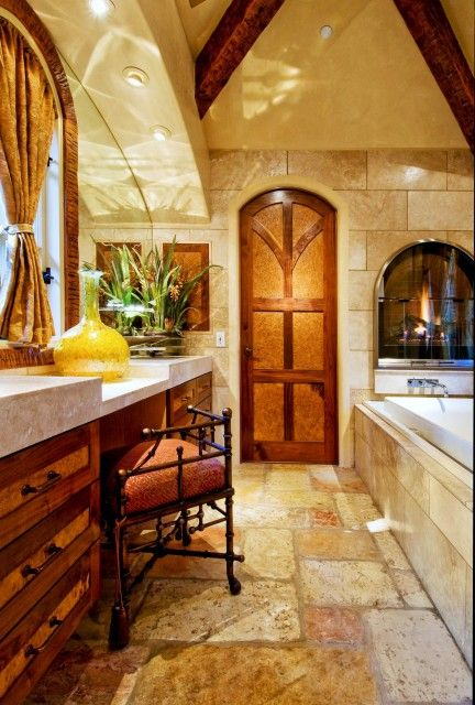 Rustic travertine tiles with the wood details on the ceiling looks awesome together!