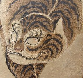 A 17th – 18th century Neko-tora Tiger by Nagasaki school artist Watanabe Shuseki performed with ink and color on paper in yellow bronze silk border with bone rollers. The parchment is aged and gray, giving the sense of a wall painting in some ancient tomb. T