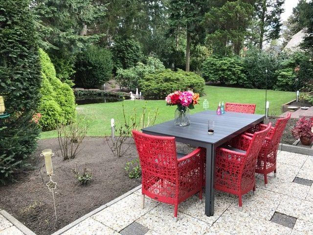 Tuinset met zwarte tafel en rode stoelen in ruime tuin