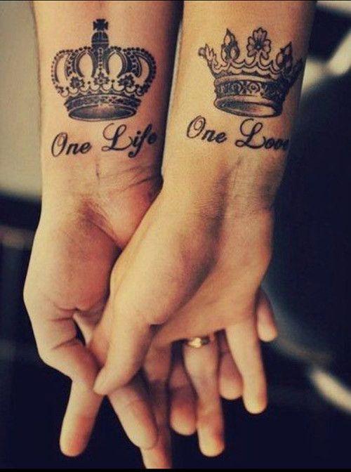 manos de una pareja entrelazadas mostrando su tatuaje en forma de coronas-Una vida un amor
