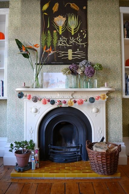 Sophie & Nick's Colourful Victorian Townhouse | bunting on fireplace, baskets in front (for blankets, etc?)