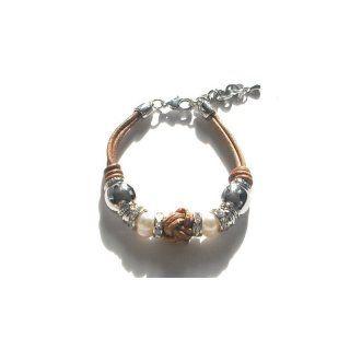 Sehr vielfältig ist dieses Echtlederarmband in braun. Es ist verziert mit siberfarbenen und strass-steinbesetzten Elementen. Dazwischen sind auch noch Kunststoffperlen zu finden. Das Armband ist größenverstellbar.
