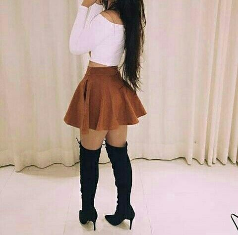 Um cropped branco e uma saia rodada marrom curta uma bota preta cano longo