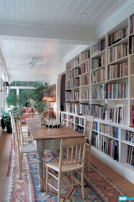 Half library, half dining, long space with white paneling and lots of natural…