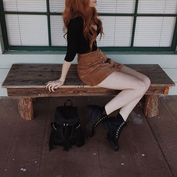 Black top and boots, with a tan suede A-line button up skirt.