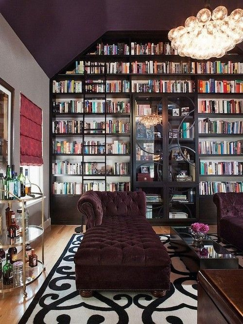 25 Stunning Home Libraries. Messagenote.com Multi-bulb chandelier, tufted lounge velvet sofa, golden bar cart, patterned black and white carpet, glass coffee table.