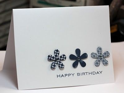 "handmade birthday card ... Clean & Simple by lorie ... line ofthree five petal flowers cut out of three different navy blue patterned papers .... ""happy birthday"" stamped below ... lots of white spece ... luv it!"