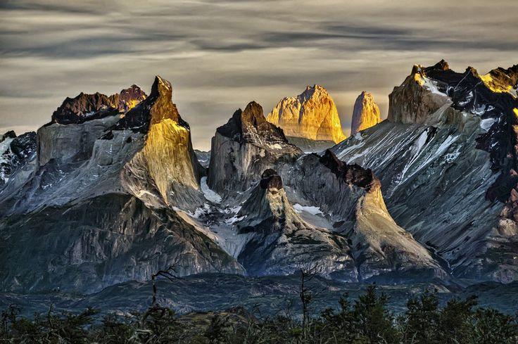 First light on Cuernos del Paine in Chile.  チリ南部のトレス・デル・パイネ国立公園で撮影された早朝の山の写真。手前の山の上部は黒色の堆積岩で、中~下部は白~灰色の花崗岩。背後の山の上部は明るい色の堆積岩。さらに一部の斜面が朝日に照らされ、残雪も点在。色の空間変化が美しい一枚。  https://twitter.com/ogugeo/status/316672217402454020