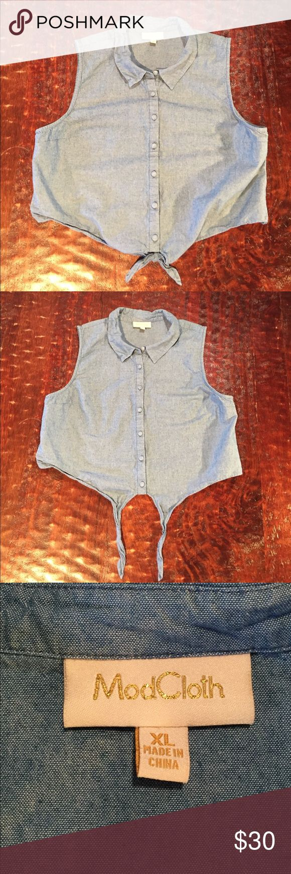 """ModCloth Denim Button Down Crop Top XL ModCloth Denim Button Down Crop Top. Top is 18"""" from shoulder to hem. Bust measures 19 1/2"""" laying flat. Crop Top is lightweight, features a tie on the bottom and is in excellent condition with no signs of wear. Comes from a Smoke Free/Pet Friendly Home. Offers always welcome. ModCloth Tops Crop Tops"""