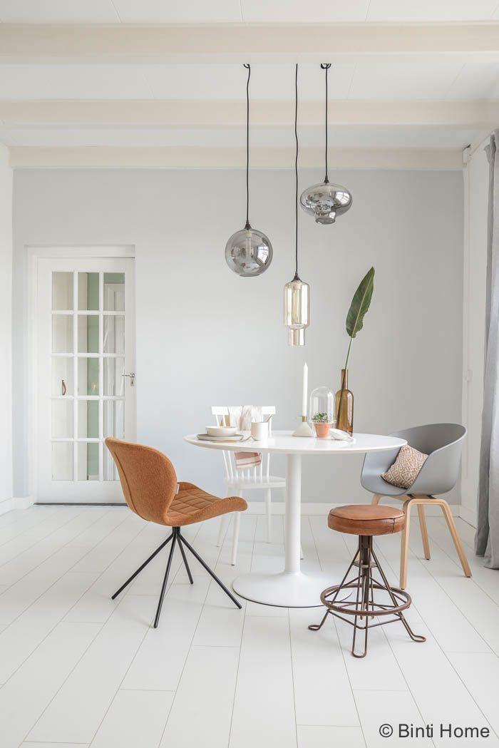 Een doorkijk naar de ronde tafel en een mix van stoelen | Binti Home blog : Interieurinspiratie, woonideeën en stylingtips