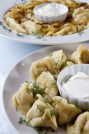 Chicken pelmeni, foreground; pierogi with potato, cheddar and dill.