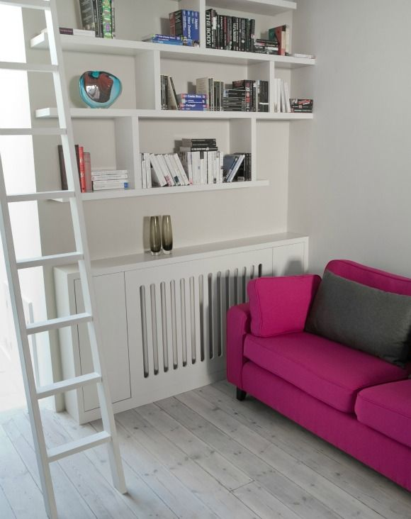 Library area with sliding ladder, with stylish radiator cover and hidden storage either side