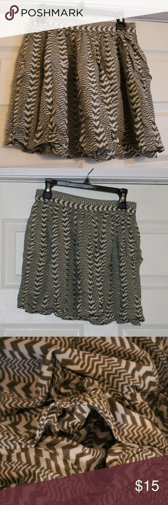 "American Eagle Olive Green/Cream Miniskirt Tags removed, NEVER WORN.  Perfect for petite girls!  Bought this skirt to wear over olive green tights with little black ankle booties.  However, I never wore the skirt before I gained weight.  Perfect for summer or in between seasons.  Paired with a leather jacket, this skirt can go from innocent to edgy. It is approximately 15"", measured from the top of the waistband to the bottom.  12.5"" waist.  I am 5' 7.5"" and the skirt is much too short on…"