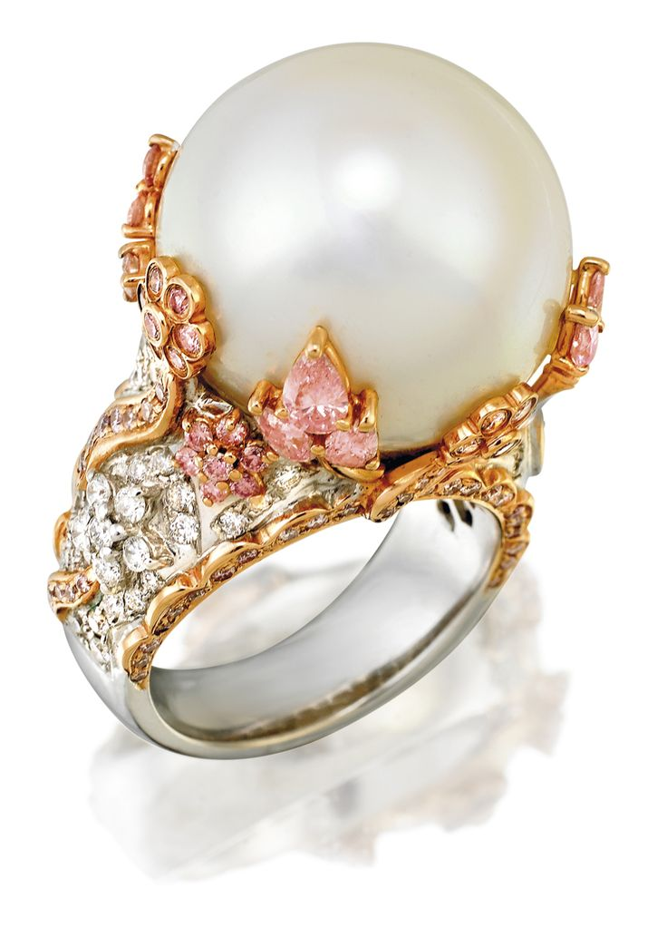 SOUTH SEA PEARL, DIAMOND AND PINK DIAMOND RING Of bombe design centring a cultured pearl measuring approximately 18.50mm on a raised surround decorated with natural fancy pink and white variously-cut diamonds, mounted in 18ct white gold, size M.