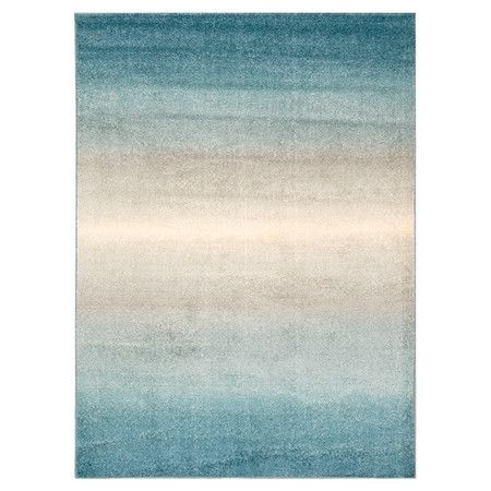 Anchor your living room decor or define a space in your master suite with this eye-catching rug, showcasing an ombre motif in blue.
