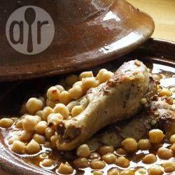 Hähnchen Tajine mit Kichererbsen - Eine wichtige Zutat für dieses Rezept ist Dersa, eine algerische Gewürzpaste aus Knoblauch, Gewürzen und Olivenöl, die für viele Fleisch-, Fisch- und Gemüsegerichte verwendet wird. Das Gericht wird zunächst auf dem Herd gegart und dann im Ofen in einer traditionellen Tajine aus Ton fertig gegart. Statt einer Tajine kann man auch einen Schmortopf verwenden. @ de.allrecipes.com