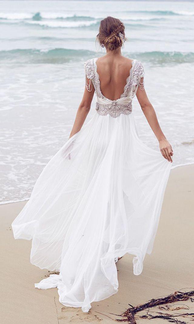 Chica con un vestido de novia con escote en la espalda caminando por la playa