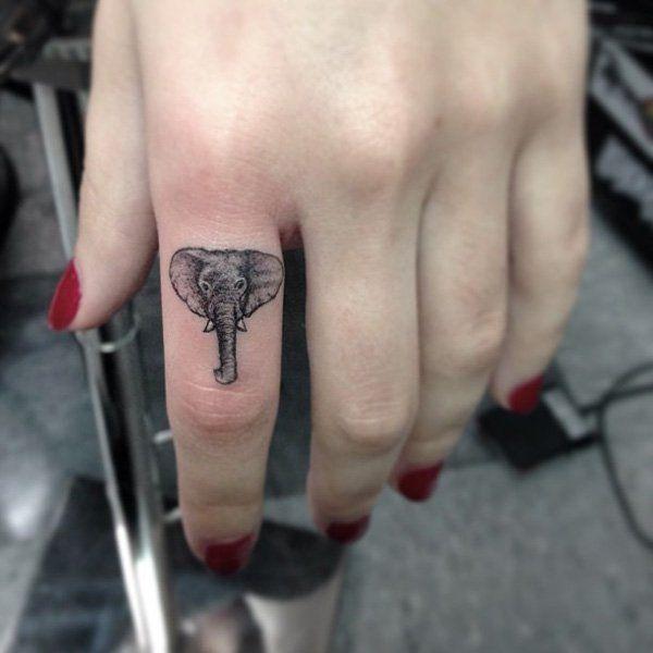 Tête d'éléphant tatoué sur le doigt d'une femme