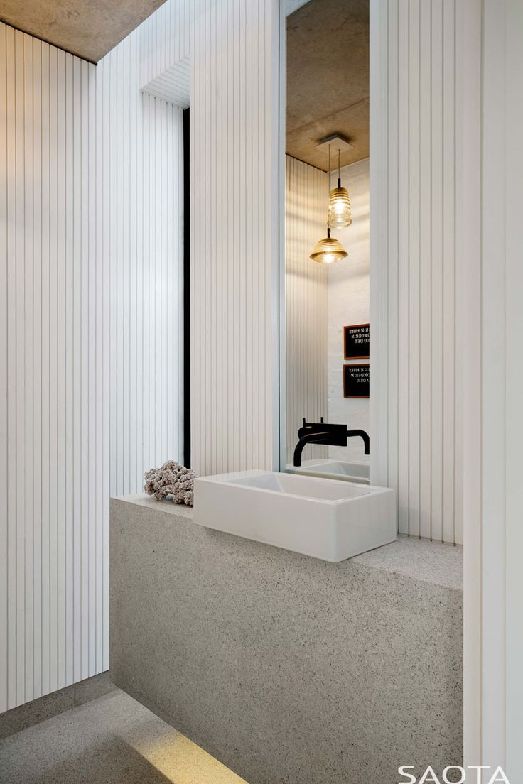 This modern bathroom has been kept bright with the use of textured white walls and a light that's hidden underneath the vanity. #Bathroom #ModernWhiteBathroom