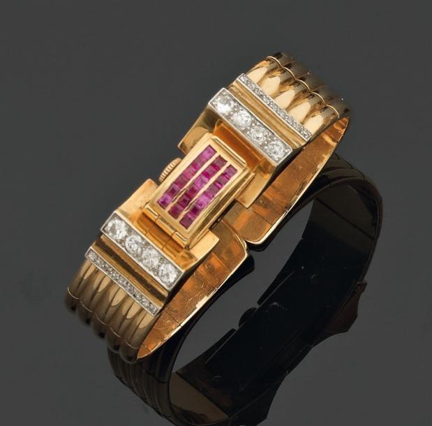 HERMES. Années 1935-1940 -     RARE BRACELET ouvert formant montre semi-rigide en ors de couleurs et platine. Deux motifs coniques sertis de diamants brillantés sont réunis par un rouleau pavé de rubis calibrés qui découvre le cadran d'une montre rectangulaire. Signé. (estimé 6000 à 8000 €)