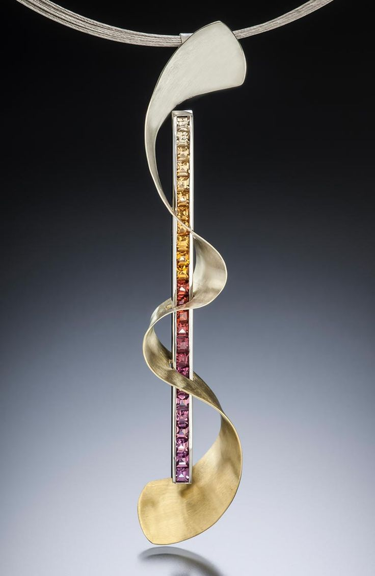 A modern pendant design by Adam Neeley.    Ombre garnet pendant is warm and elegant. In this unique pendant design, a sumptuous selection of garnets, across spessartite and rhodolite color ranges, coupled with a curving form of color-gradient Spectra gold.