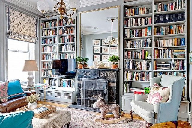 A living room with a wall of books, a fireplace and a large vintage mirror