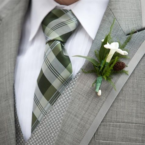 My winter wedding made TheKnot.com! Our groomsmen wore grey tuxes that looked more like suits...we didn't want it too formal for our rustic day. Our colors were sage green and ice blue and the wedding was on St. Patrick's Day so plaid was a must. Stephanotis and Pinecone Boutonniere