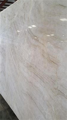 Taj Mahal quartzite for kitchen and bathroom countertops. Light cream and faint brown veining with an overall swooping motion. #creamy #quartzite #countertops