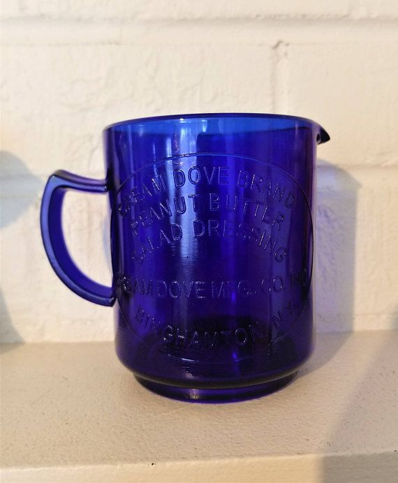 Beautiful cobalt blue measuring cup, a one cup measure with markings in two ounce increments and 1/4 cup increments. Opposite side reads Cream Dove Brand Peanut Butter Salad Dressing ~ Cream Dove Mfg. Co. Inc. ~ Binghamton N.Y. 3 3/4 inches high and 3 1/8 inches in diameter. no chips