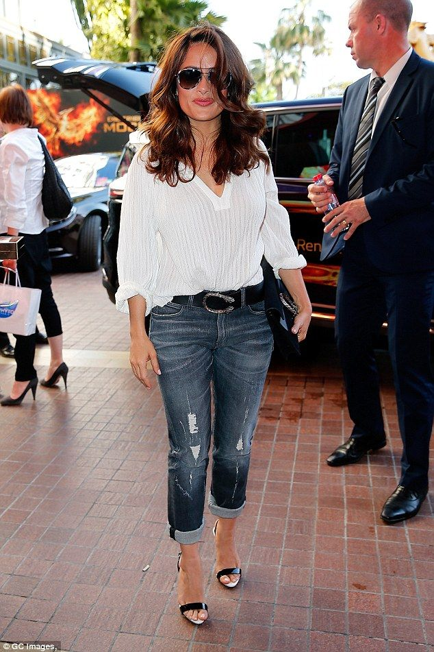 Off-duty-chic: Salma Hayek proved she can look just as stylish in a simple white blouse and baggy jeans as she was seen out and about in Cannes on Saturday