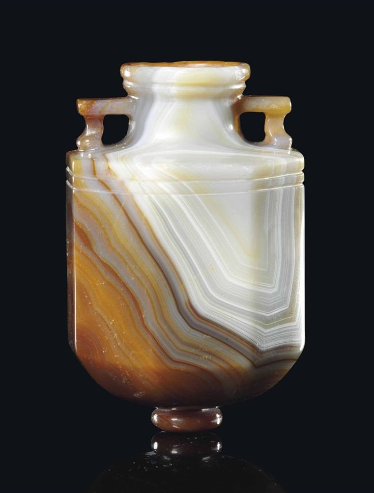 A ROMAN BANDED AGATE AMPHORISKOS, CIRCA 1ST CENTURY B.C. - 1ST CENTURY A.D. Octagonal in form, with thick walls, the interior deeply hollowed, short tapering cylindrical neck with overhanging disk rim, with stepped underside, angled handles, two wheel-cut bands beneath shoulders and knopped base. 2.3/8 in. (6 cm.). -Christie's-