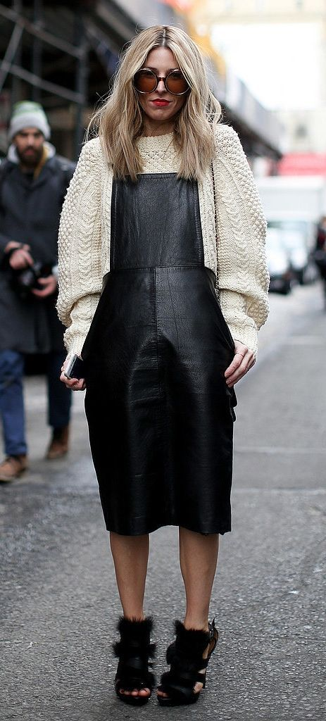 Black leather dungarees worn with a cream jumper