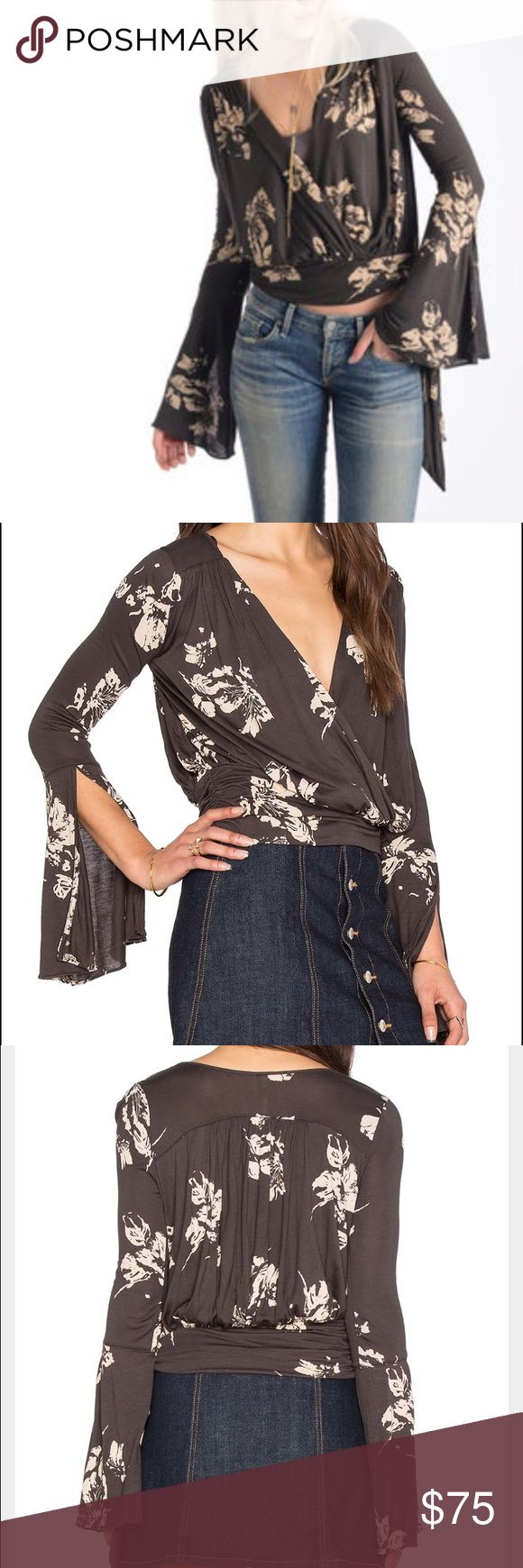 NWOT Free People Fiona Wrap Top NEW WITHOUT TAGS. Free People fiona wrap top with bell sleeves. Ties at the side. Grey with pale pink floral design. Never worn! Free People Tops Blouses