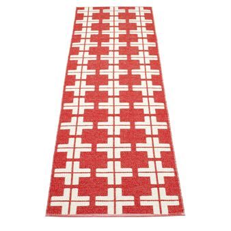 Klas rug in red and white is a colorful carpet with a graphic pattern. A woven plastic rug from Swedish Pappelina.