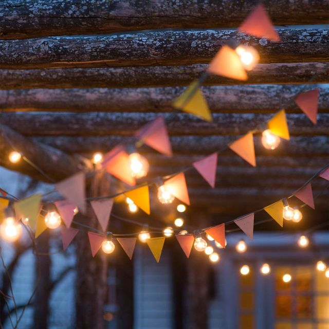 Mix string lights with colorful bunting, both courtesy of Terrain.
