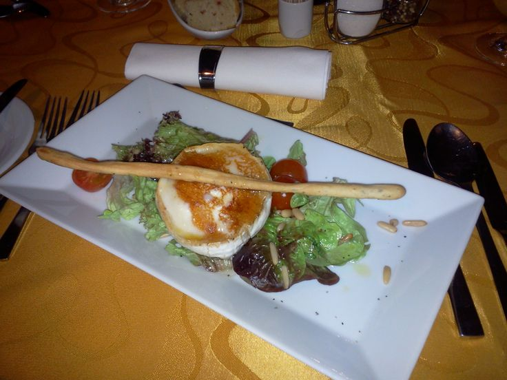 Grilled goat cheese with honey and pine nuts served on lettuce